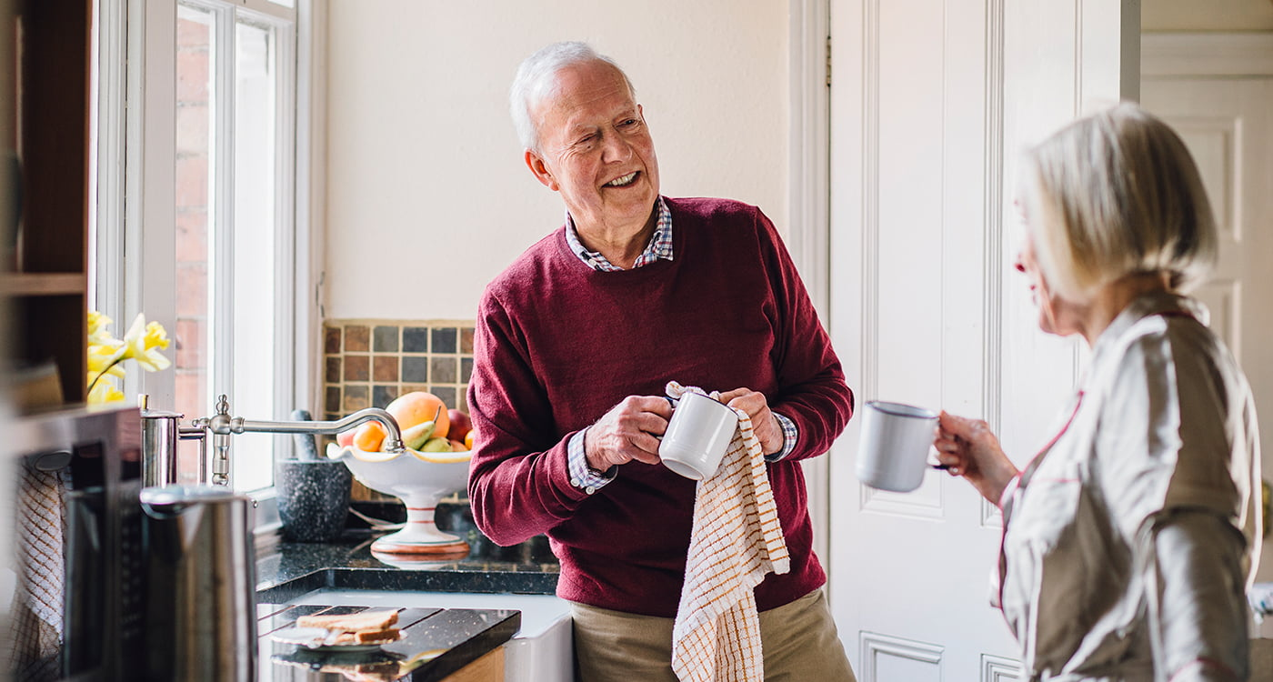 an older man talking to a woman while wiping dishes in the kitchen