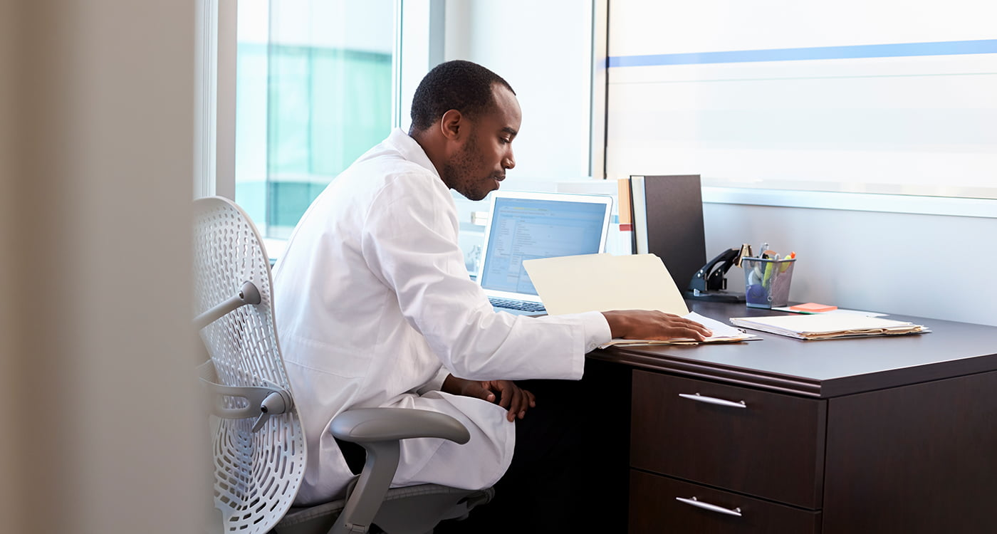 a doctor sitting as his desk looking in a folder